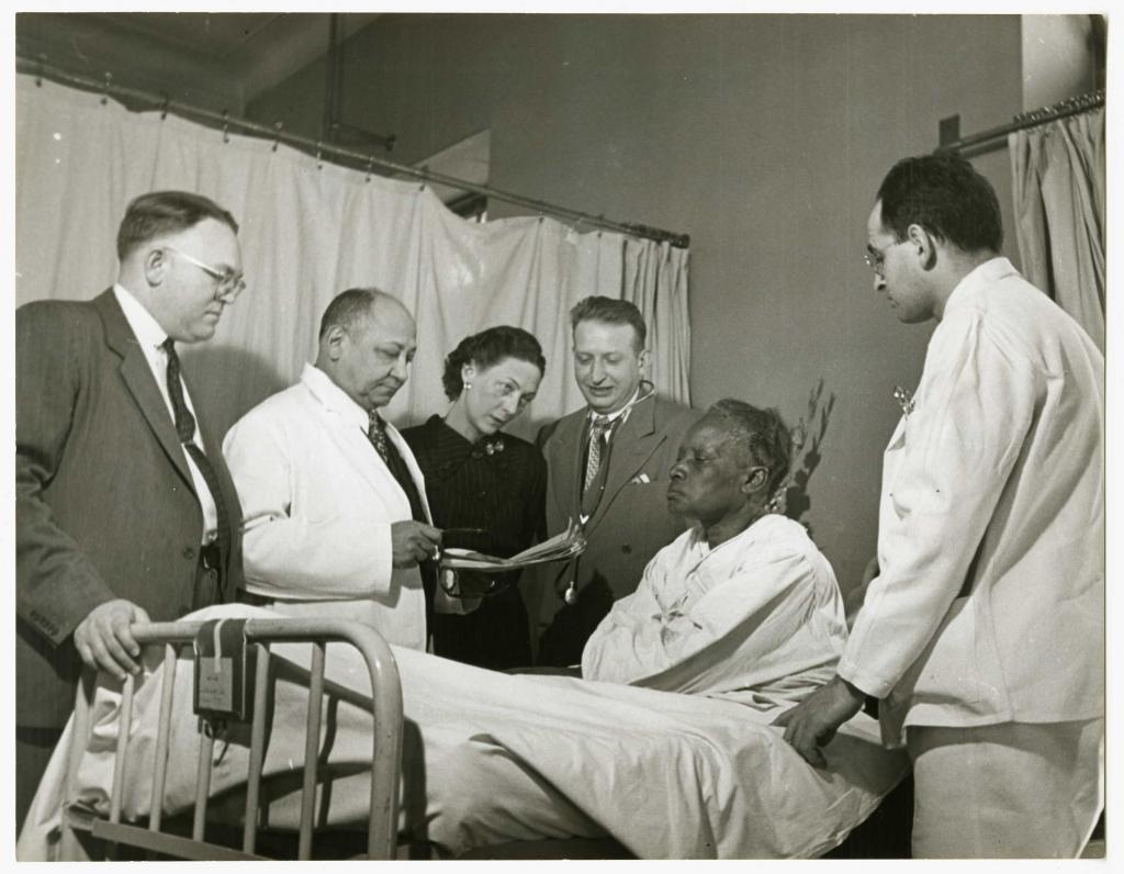 Black and white photograph of three men and one woman standing at the bedside of an African American woman, who is sitting up in the bed. Two of the men are dressed in suits and are peering at a clipboard held by a man in a white coat. The standing woman is wearing a dark dress and looking at the woman in the bed. In the foreground is a man dressed in white scrubs.