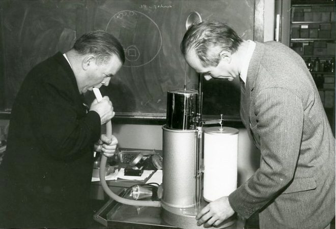 Two people measure respiration using a spirometer in 1961.
