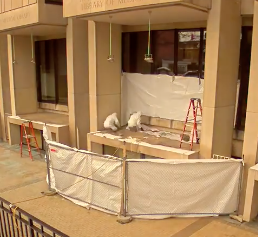 outside fenced portion of the library with three construction men wearing white clothes.