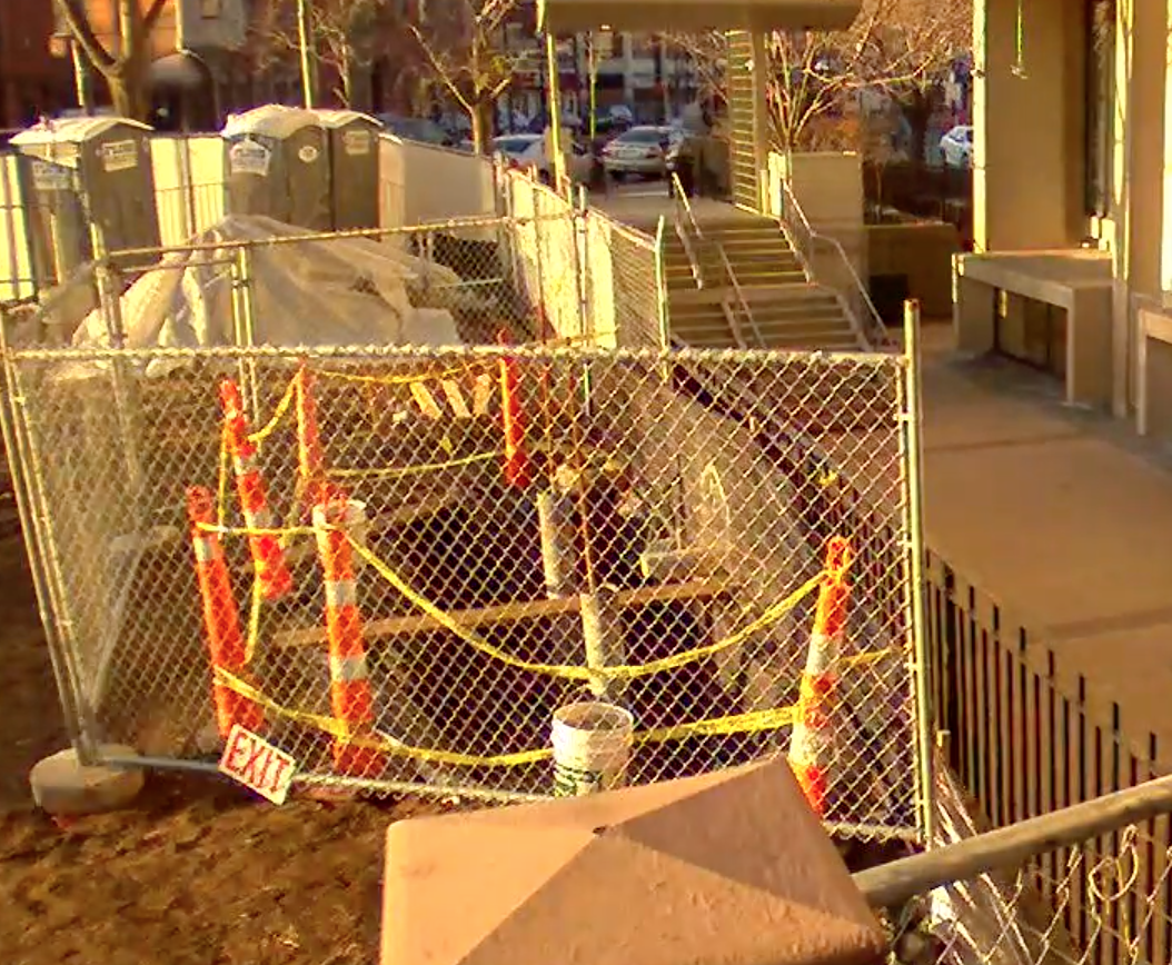 gated construction area outside of library with orange construction cones and caution tape