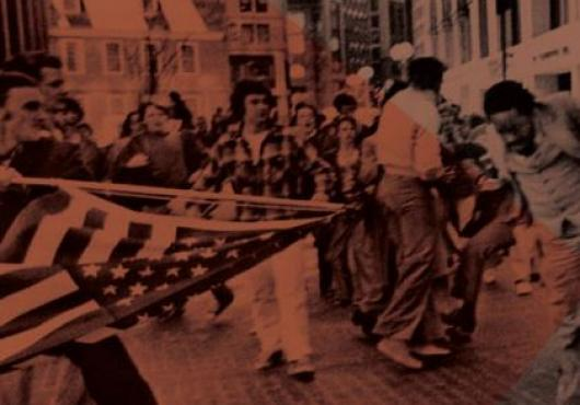 Photograph of a protest with man waving an American flag